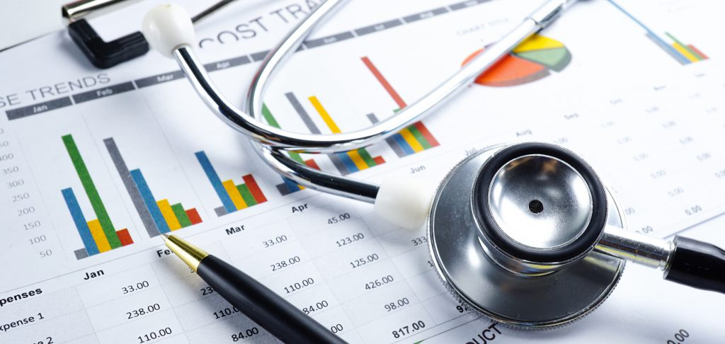 Stethoscope and pen laying on printed HEDIS® data charts.