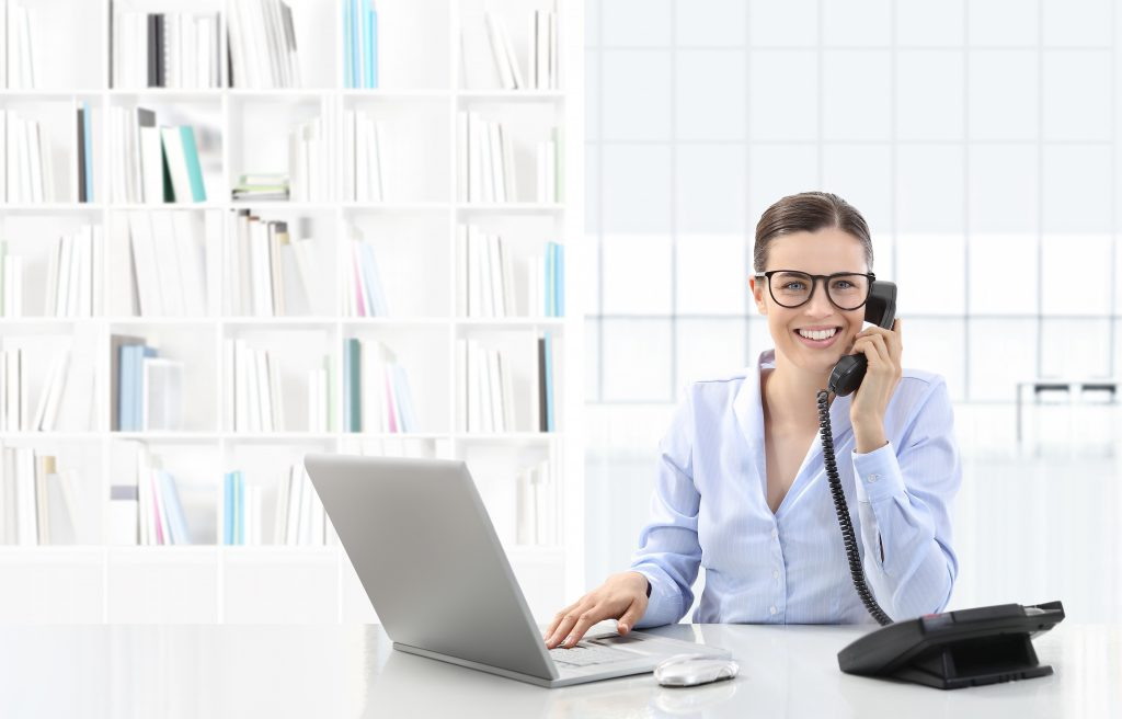 Business woman uses laptop and talks on phone to Contact KDJ.